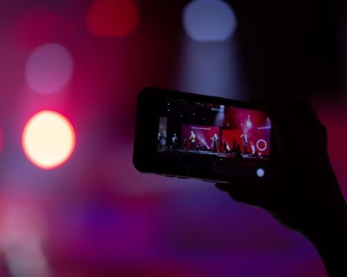 close up of hand holding a mobile phone streaming a music festival
