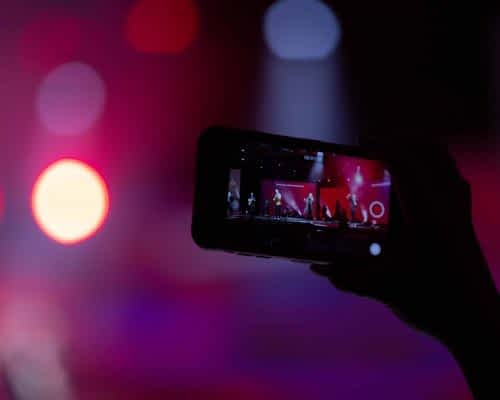 close up of hand holding a mobile phone streaming a music festival - jawbone live stream concert 2 virtual digital event management